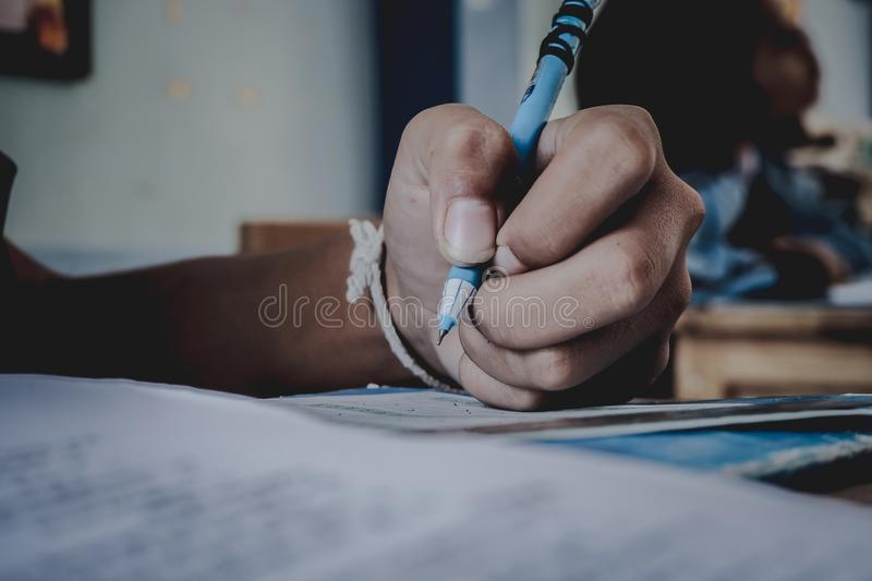 Closeup to hand of student holding pen and taking exam in classroom with stress for education test. stock photos