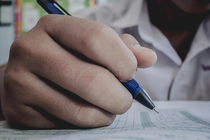 Closeup to hand of student holding pen and taking exam in classroom with stress for education test. royalty free stock images