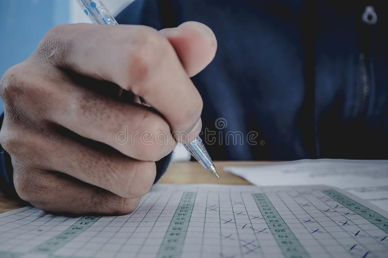 Closeup to hand of student holding pen and taking exam in classroom with stress for education test. stock image