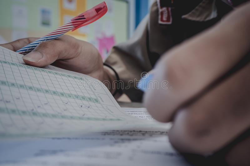 Closeup to hand of student holding pen and taking exam in classroom with stress for education test. royalty free stock photos