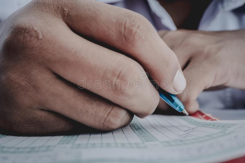 Closeup to hand of student holding pen and taking exam in classroom with stress for education test. royalty free stock photography