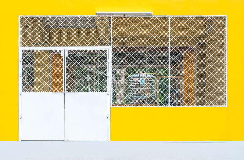 Closeup to Metal Entrance Door of Concrete Yellow Factory Warehouse.  royalty free stock photography