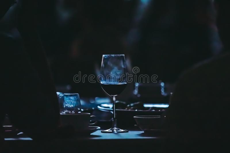 Closeup to wine glass at night party of wedding ceremony in dark tone. stock photos