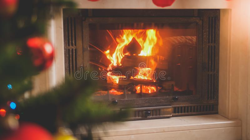 Closeup toned image of fire flames in fireplace next to decorated Christmas tree at house. Closeup toned photo of fire flames in fireplace next to decorated stock photos