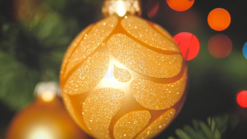 Closeup toned photo of golden baubles hanging on Christmas tree branch against glowing lights garlands. Perfect stock image