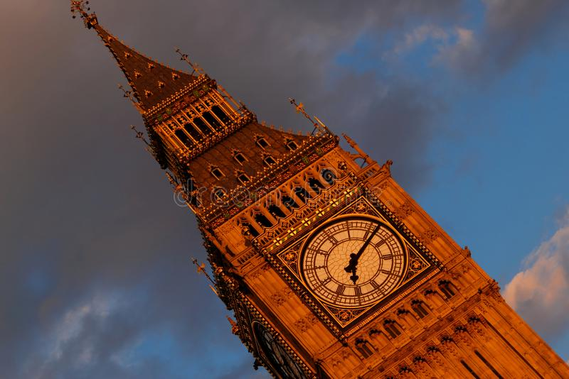 Closeup of top of Elizabeth Tower also known as Big Ben showing clock face in late evening sun with blue sky and grey cloud in bac royalty free stock image