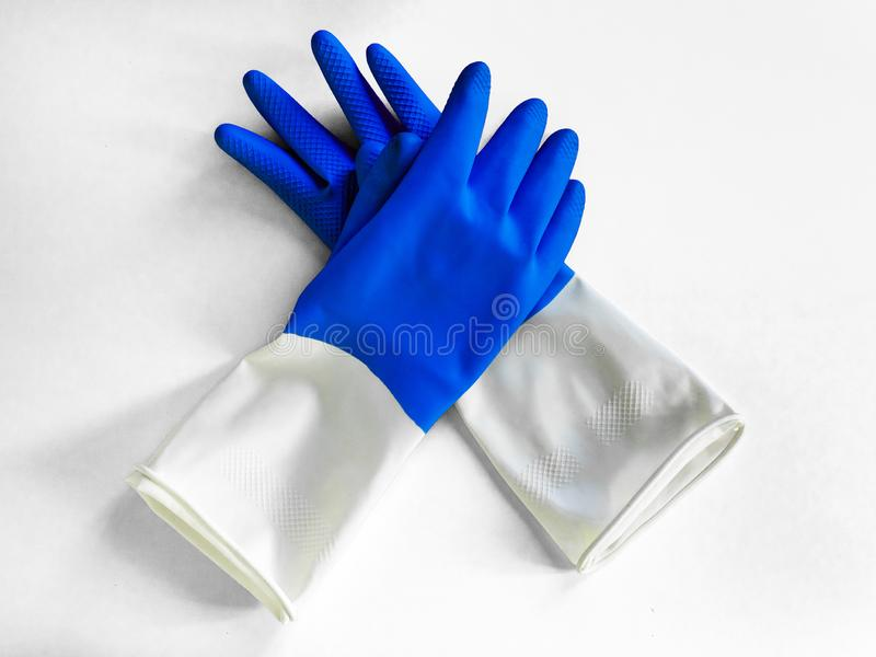 Closeup top view of beautiful blue rubber gloves on white background. housework concept. General or regular cleanup. Commercial stock photo