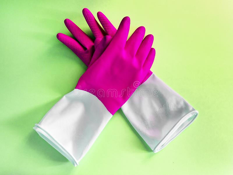 Closeup top view of beautiful pink latex gloves on green background. housework concept. General or regular cleanup. Commercial royalty free stock photography