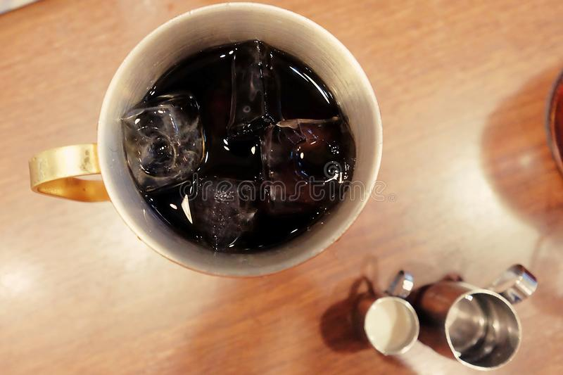 Closeup top view ice of americano, Iced black coffee contained in a copper cup served with syrup and fresh milk royalty free stock image