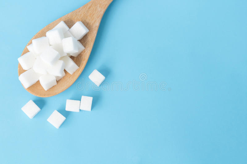 Closeup top view sugar cubes on wooden spoon white blue background royalty free stock photo