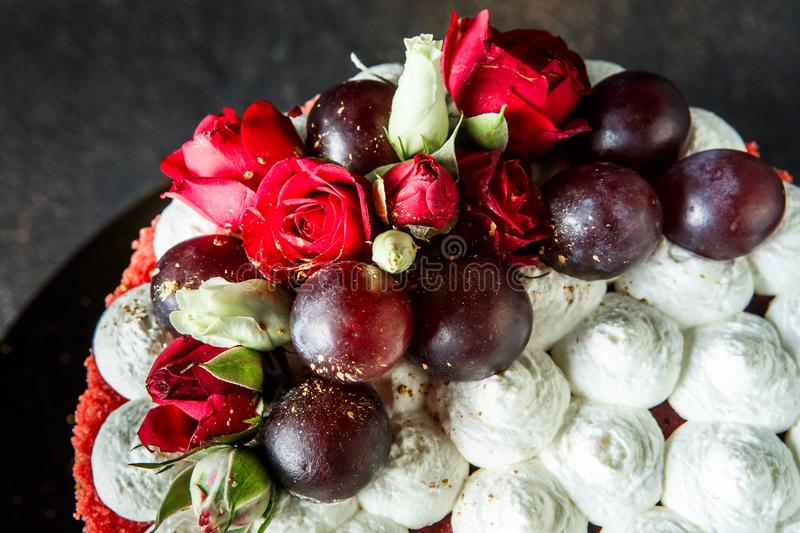 Closeup topping of cake decorated with bizet, grapes and roses. Closeup topping of beautiful cake decorated with white bizet, grapes and roses stock photos