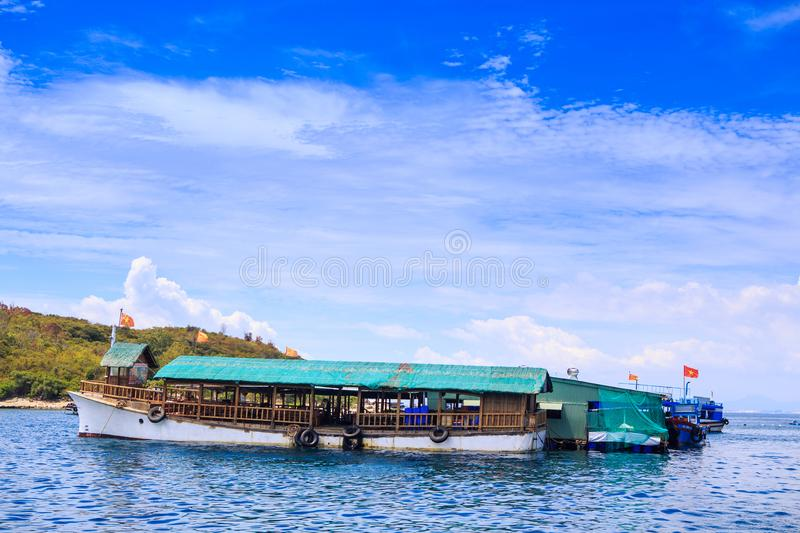 Closeup Tourist Motorboat at Moorage by Coast Clouds Sky. Closeup large tourist motor-boat at moorage near green hills shore against white clouds lace in blue royalty free stock photo