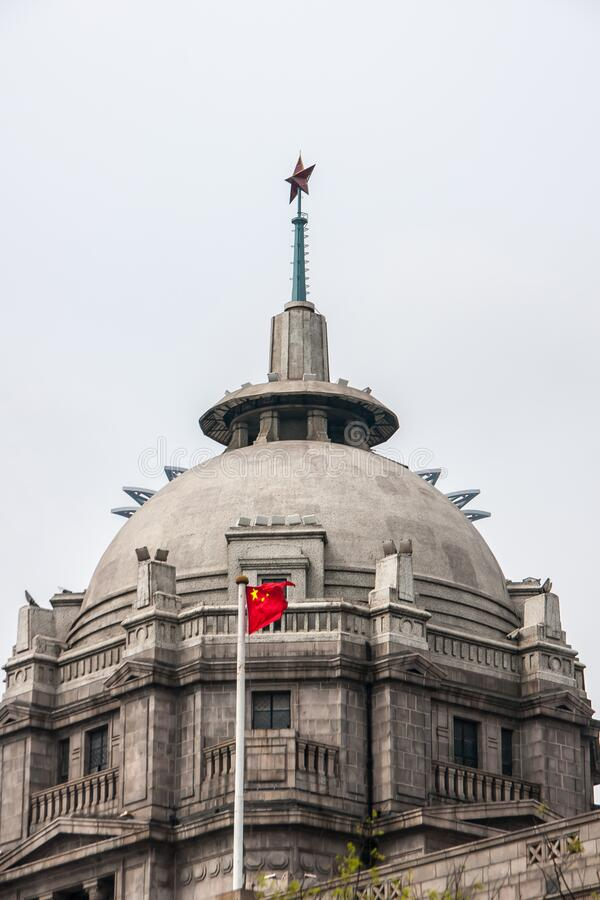 Closeup of tower and dome of HSBC building along Bund, Shanghai, China. Shanghai, China - May 4, 2010: Closeup of gray-brown top with dome of HSBC bank with red stock image