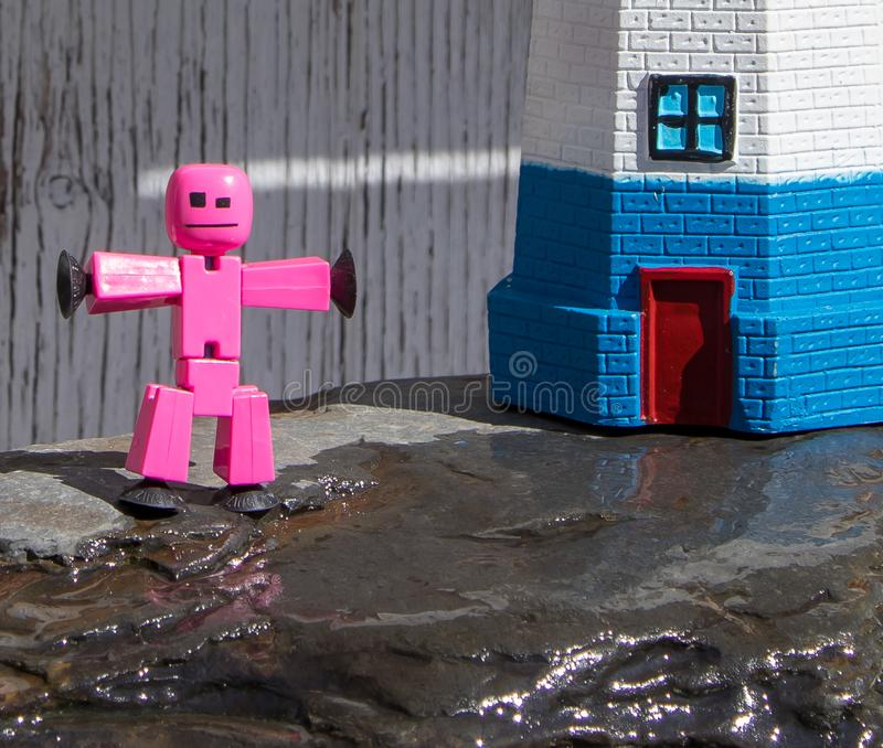 Closeup of toy stick figure playing on wet rocks. Closeup of toy stick figure playing on wet rocks at the foot of a plastic lighthouse stock photos