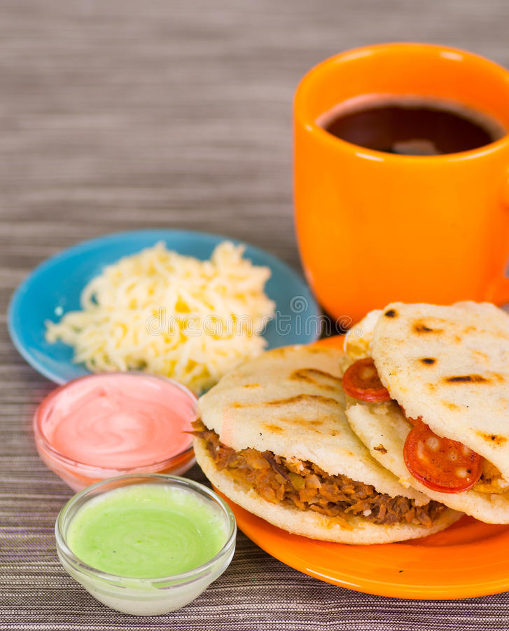 Closeup of a traditional delicious arepas, shredded chicken avocado and cheddar cheese and shredded beef with grated. Cheese, avocado and pink sauce in bowl on stock photos