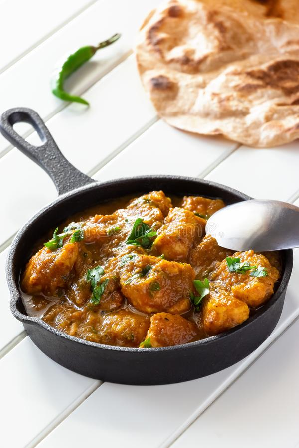 Closeup traditional Indian butter chicken curry and lemon served with chapati bread in iron-cast. Wooden background royalty free stock image