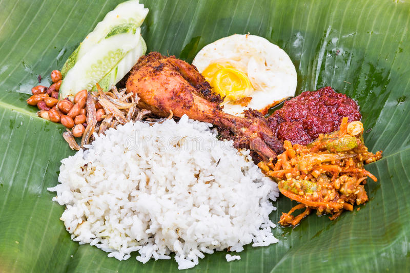 Closeup on traditional nasi lemak cuisine on banana leaf with fried chicken. Closeup on traditional nasi lemak meal on banana leaf with fried chicken, anchovies royalty free stock photos