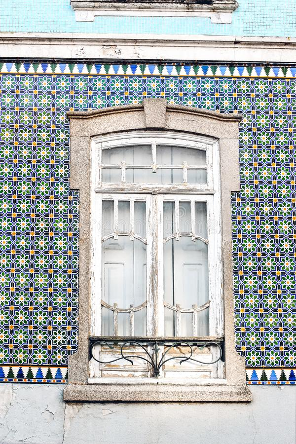 Closeup of traditional Portuguese house facade decorated by beautiful ceramic azulejo tiles Old white wooden window on. Tile painted wall. Portugal town, Europe royalty free stock images