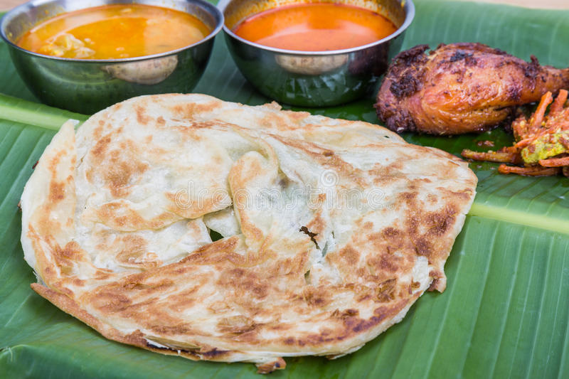 Closeup on traditional roti prata served on banana leaf with curry dhal. stock images