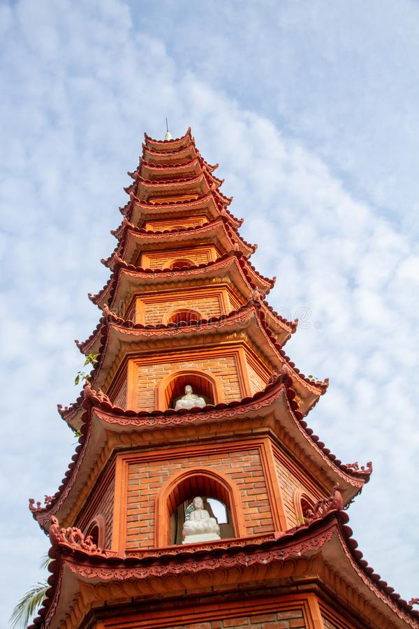 Closeup of the Tran Quoc Pagoda against a blue sky with whisky white clouds, Hanoi, Vietnam. Closeup of the beautiful red and orange repeating roofline of the stock images