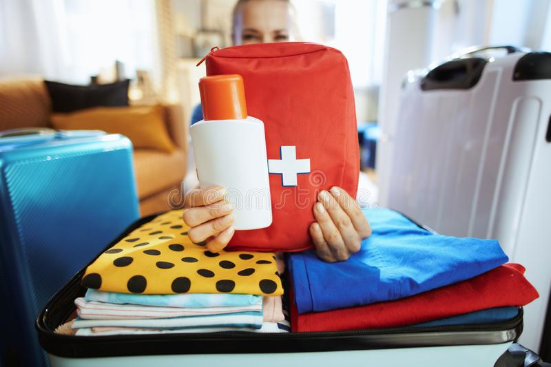 Closeup on traveller woman showing sunscreen and first aid kit. Closeup on modern traveller woman in blue t-shirt in the modern living room in sunny summer day royalty free stock photo