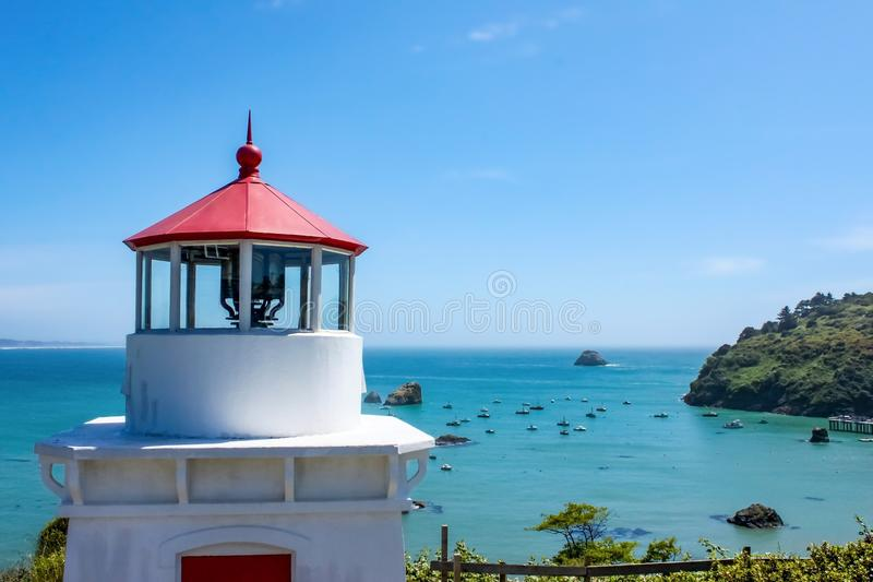 Closeup of Trinidad Head Lighthouse overlooking Trinidad bay California with boats anchored down below royalty free stock image