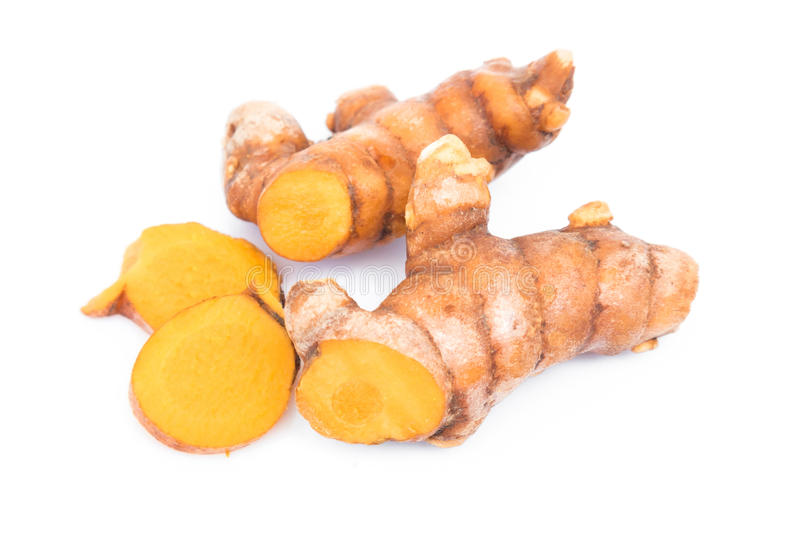 Closeup turmeric roots slices on white background stock photo