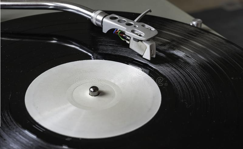 Closeup turntable player playing vinyl record disc. royalty free stock images