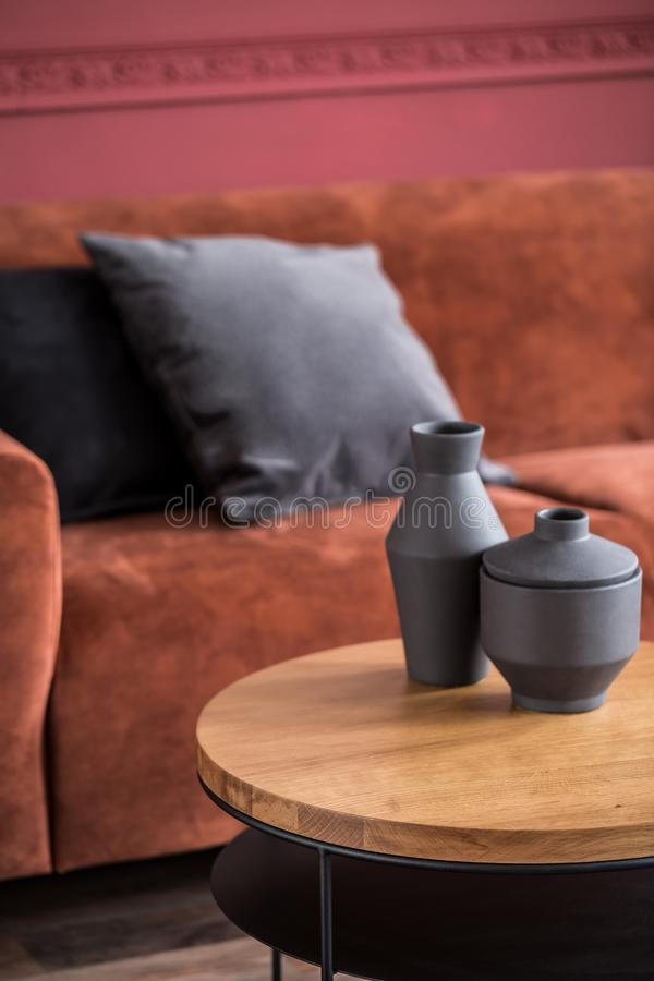 Closeup of two black vases on round wooden coffee table in elegant living room interior royalty free stock photos