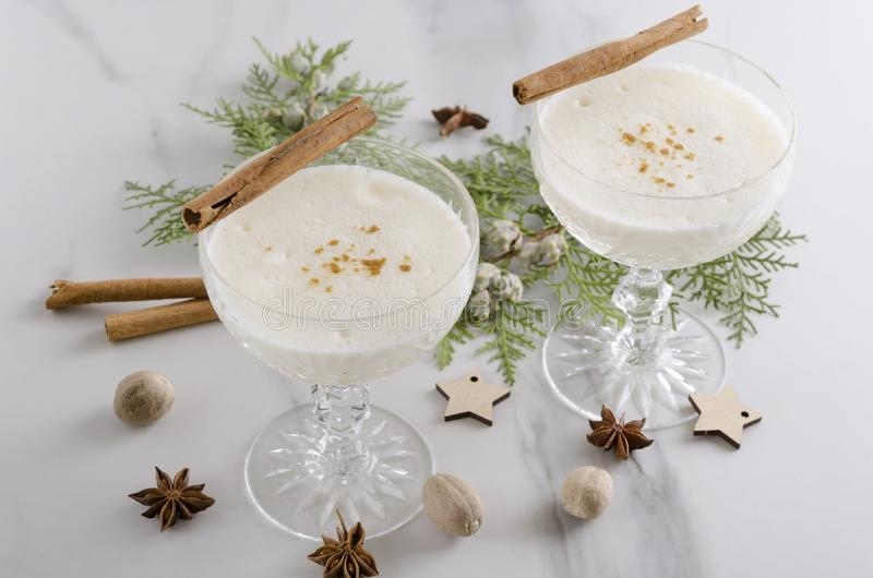 Closeup of two cocktail glasses of aromatic tasty eggnog with alcohol, cinnamone sticks, nutmeg.Delicious traditional Christmas dr royalty free stock photos
