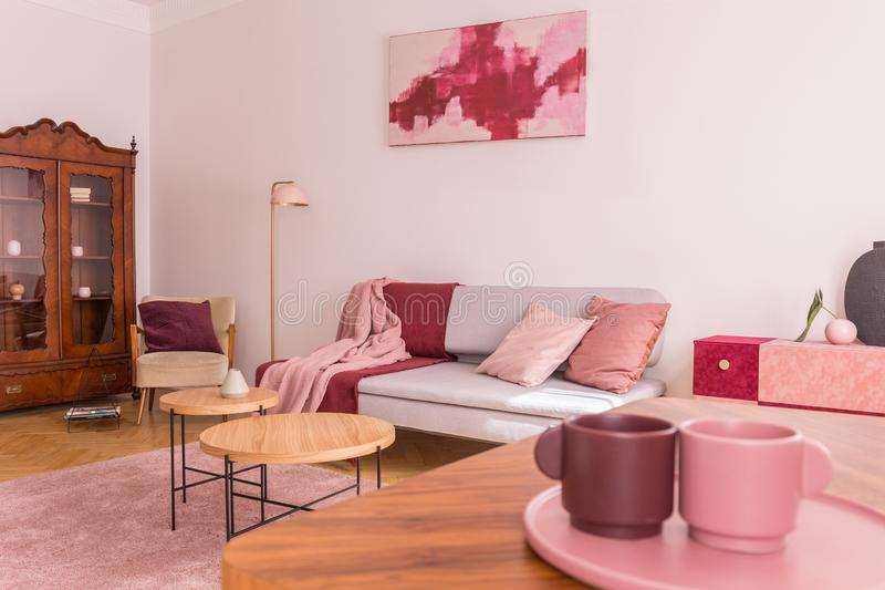 Closeup of two coffee cups on the table in elegant living room with grey couch with pastel pink pillows, stylish armchair and. Vintage cabinet concept photo royalty free stock photo