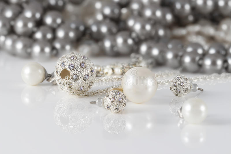 Closeup two jewelry sets of studded silver and pearls earrings. stock photos