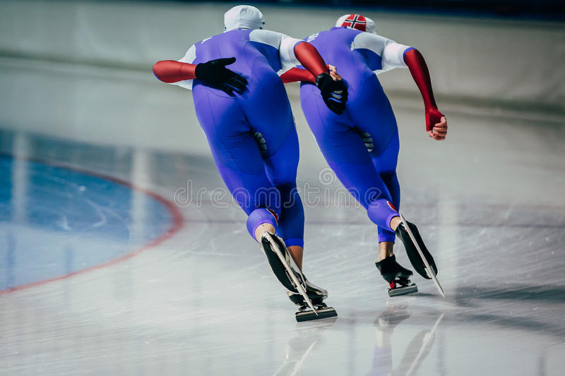 Closeup two men skaters synchronous running royalty free stock image