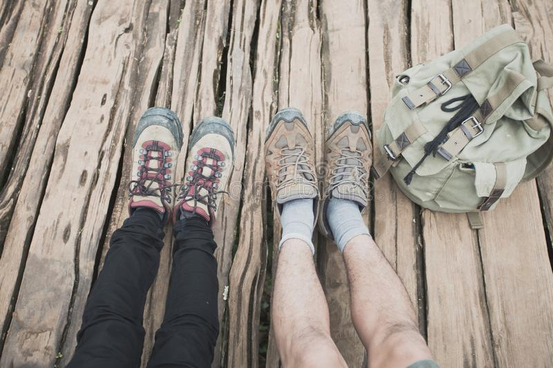 Closeup two pairs of feet in hiking shoes stick out.Two pairs of. Hiking boots stock image