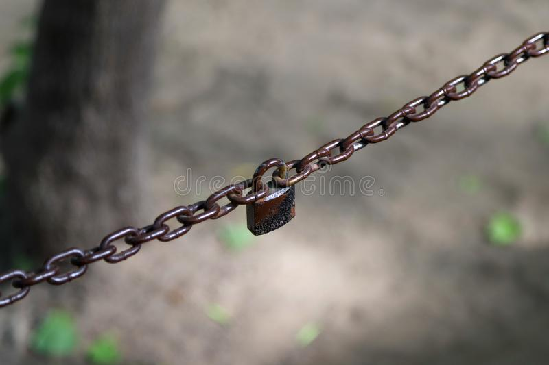 A two-parted brown chain connected with an old rusty padlock. Closeup of a two-parted brown chain connected with an old rusty padlock royalty free stock photos