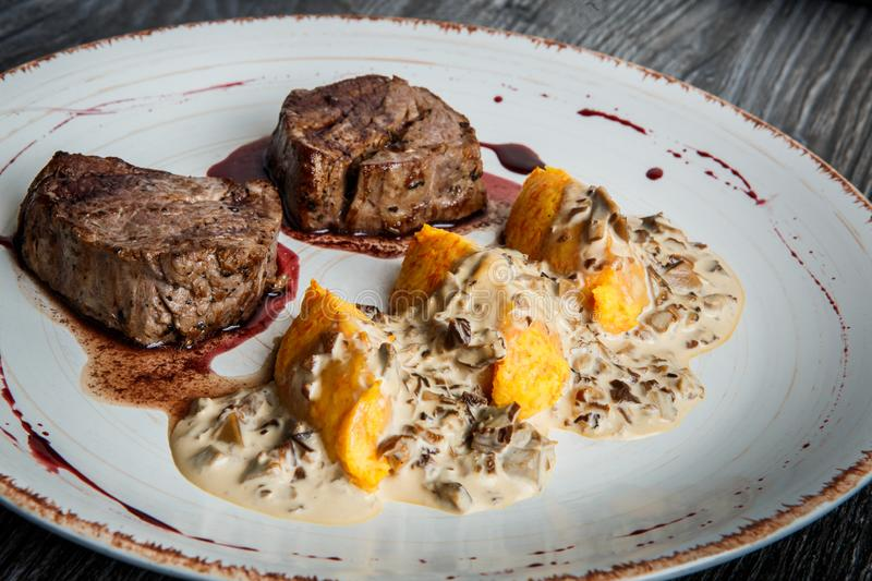 Closeup two pieces of grilled meat steak with blood with potato zrazy royalty free stock photography