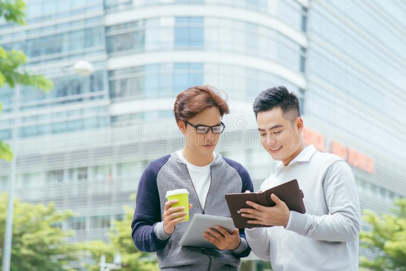 Closeup of two smiling business men using tablet computer and walking with office building in background - Image stock image