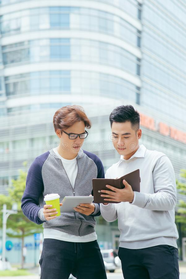 Closeup of two smiling business men using tablet computer and walking with office building in background - Image stock images
