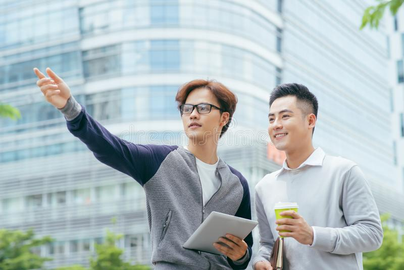 Closeup of two smiling business men using tablet computer and walking with office building in background - Image stock photo
