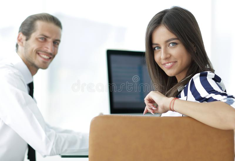 Two young employee sitting behind a Desk. Closeup.two young employee sitting behind a Desk royalty free stock images