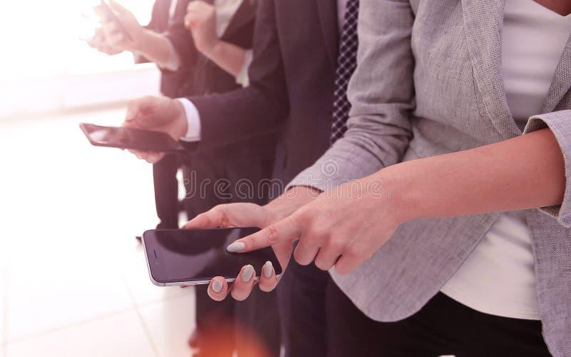 closeup un gruppo di impiegati con gli smartphones fotografia stock