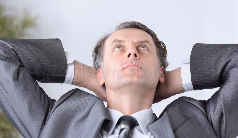 closeup un riuscito relaxarea dell'uomo d'affari che si siede dietro uno scrittorio immagine stock