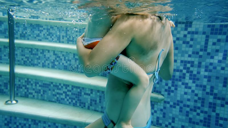 Closeup underwater image of little toddler boy with young mother relaxing in swimming pool royalty free stock photo