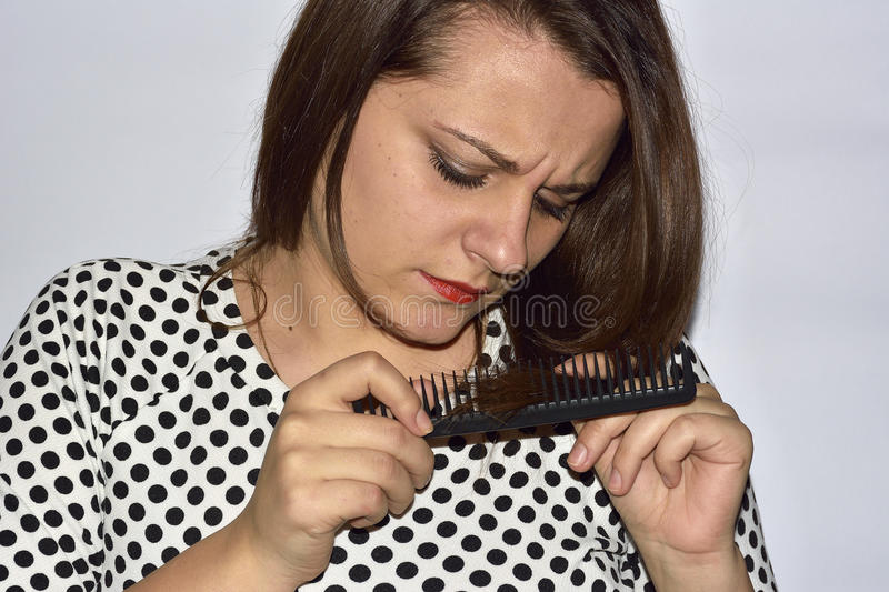 Closeup unhappy frustrated young woman surprised she is losing hair, noticed split ends receding hairline. Human. Closeup unhappy frustrated young woman royalty free stock photo