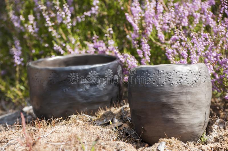 Closeup of unique handmade black pottery planters in sunlight and heater blossoms on background. Autumn mood with beautiful closeup of unique handmade black stock image