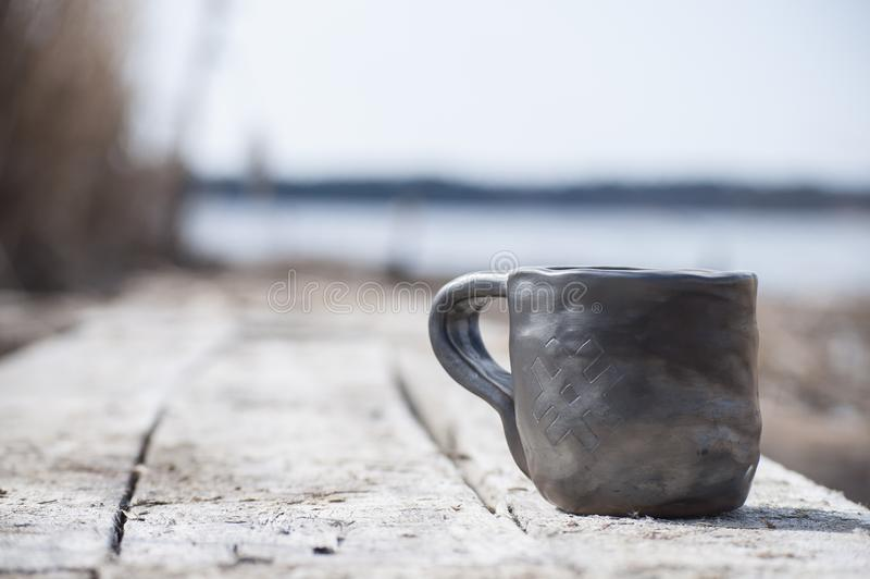 Closeup of unique handmade cup with folk sign with blurred lake on background. Beautiful closeup of unique handmade cup with folk sign with blurred lake on stock photography