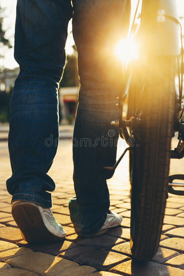 Closeup Unrecognizable Male Feet And City Bicycle Wheels, Rear View And Low Angle Holiday Weekend Activity stock image