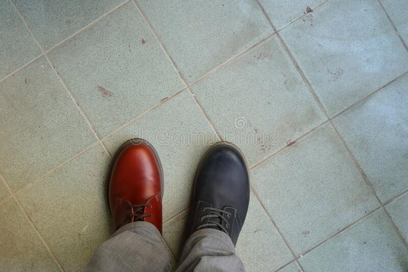 Wearing mismatched shoes is not illegal. Closeup upper of mismatched shoes, a man wearing two different shoes and different colors standing on tiled floor, break royalty free stock image