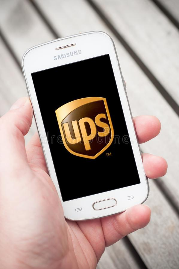 Closeup of UPS logo on smartphone in hand in the street royalty free stock photography