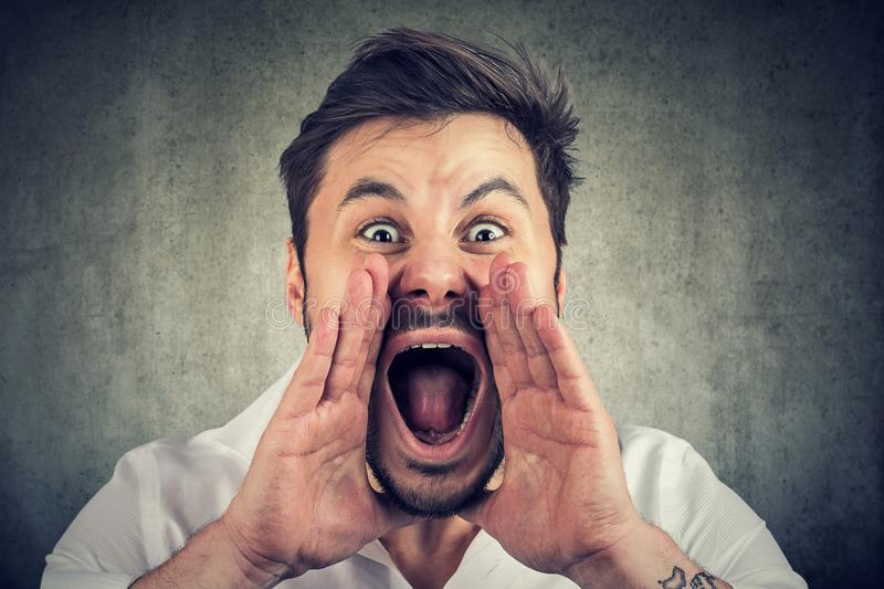 Closeup of upset, angry man with hands close to wide opened mouth yelling stock photos